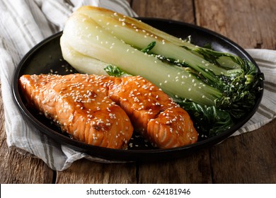 Glazed salmon fillet with sesame seeds and roasted cabbage bok choy close-up on a plate. horizontal