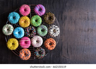 Glazed sweet mini donuts on wooden background with blank space