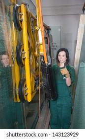 Glazier in glass storage or warehouse operating a crane