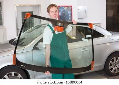 Glazier handling car windshield or windscreen made of glass in garage
