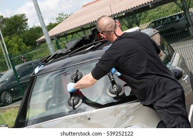 Glazier handling car windshield or windscreen made of glass in garage