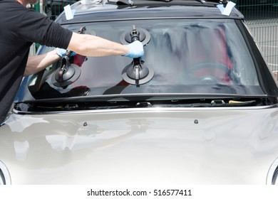 Glazier removing windshield on a car