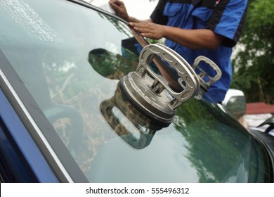 Glazier repairing, fixing broken windshield car. insurance agents replacing windscreen Mountings. glazier replacing broken glass mounting repair windshield, windscreen. insurance agents claim concept.