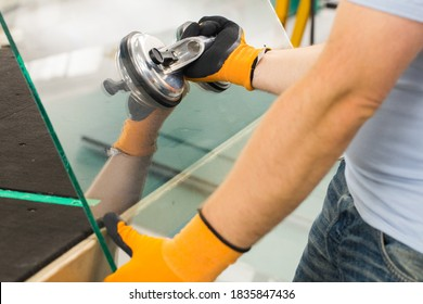 The Glazier uses a sucker for windows. Glass making workshop, The man lifts the pane of thick glass on the table with the help of specialized tools