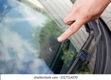 Glazier windscreen on Broken car windshield glass from stone pointed watch of finger hand