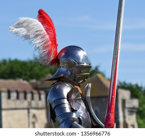 A gleaming knight in armour from side profile, preparing to joust, with Leeds Castle, England in soft-focus in the background.