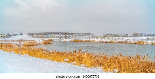 A gleaming lake with grasses lining the shore in Daybreak Utah in winter