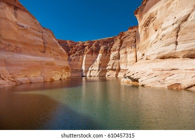 Glen Canyon coloured sandstone cliffs filled with water, near Lake Powell and the Colorado River, straddling the border between Utah and Arizona. National park and popular tourist attraction.