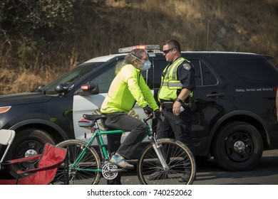 GLEN ELLEN, CALIFORNIA/ USA - OCT 16, 2017: A resident of Glen Ellen waits by a CHP officer at a road block. Fires in California have burned over 220,000 acres and destroyed 5700 structures.