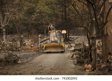 GLEN ELLEN, CALIFORNIA/ USA - OCT 16, 2017: A bulldozer clears a path in a destroyed Sonoma county neighborhood. Fires in California have burned over 220,000 acres and destroyed 5700 structures.