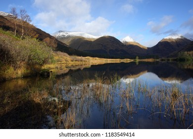 Glen Etive in November with snow on the summit of Buachaille etive mor and clouds casting shadows on the hills.