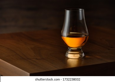 Glencairn glass with scottisch single malt whisky on wooden taböe