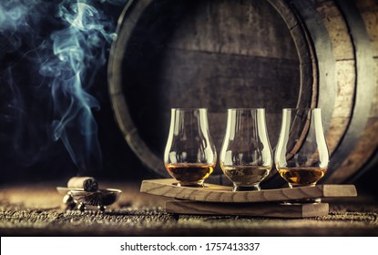 Glencairn whiskey tasting cups on a wooden serving, with a whisky barrel in the dark background and a smoking cigar next to it.