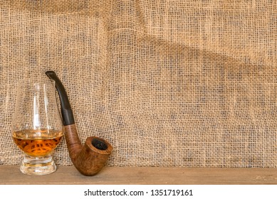 Glencairn whisky glass and pipe against a burlap backdrop for mock ups and copy space