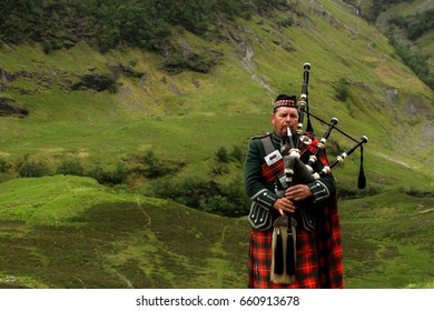 GLENCOE, SCOTLAND - JUNE 25, 2015: Bagpiper in national clothes against the background of the mountains of Scotland