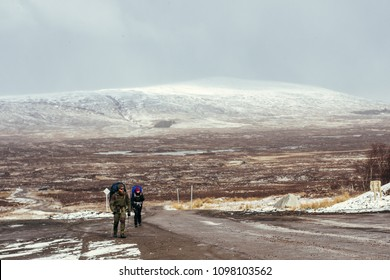Glencoe,Scotland/UK - 03.17.2018: climbers walking along the road which is lead to the Glencoe Ski area, located on a very isolated stretch of the A82 amongst some of the most dramatic scenery in UK