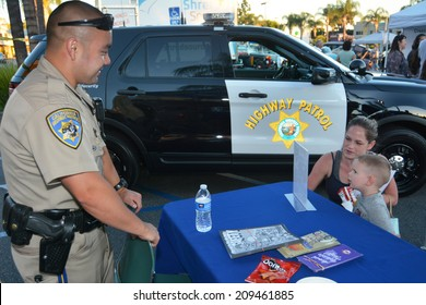GLENDALE, CA - AUGUST 5, 2014: A mother and child discuss crime prevention with California Highway Patrolman at a National Night Out community fair in Glendale, California on August 5, 2014.