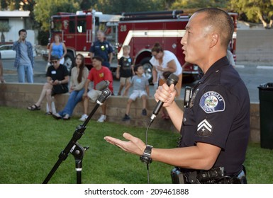 GLENDALE, CA - AUGUST 5, 2014: A police officer at a microphone discusses neighborhood crime prevention with community members at a National Night Out against crime community fair.