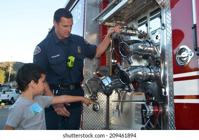 GLENDALE, CA - AUGUST 5, 2014: A firefighter explains his job to young boy pointing at his fire truck as part of a National Night Out against crime community fair.