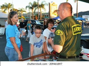GLENDALE, CA - AUGUST 5, 2014: A family discusses crime prevention with a member of the Los Angeles County Sheriff's Department at a National Night Out against crime community fair.