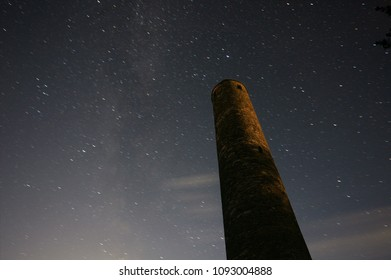 Glendalough round tower in Ireland with constellation at night