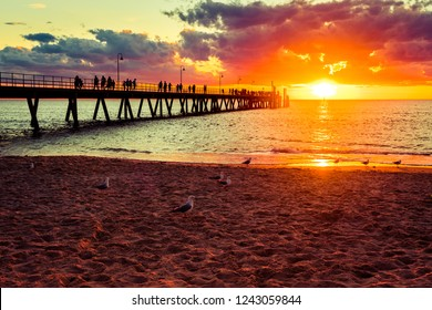 Glenelg beach with people walking along jetty at sunset, South Australia.