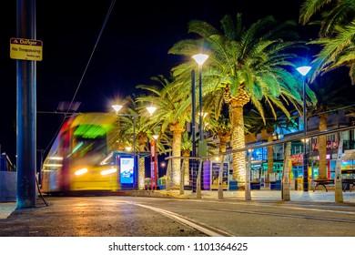 Glenelg, South Australia - July 1, 2017: Adelaide Metro tram on Moseley Square stop heading towards CBD at night. Long exposure effect.
