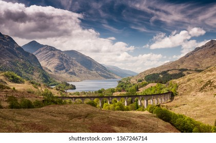 The Glenfinnan Viaduct carries the West Highland Railway Line high above Glen Finnan valley beside the lochs and mountains of Scotland.