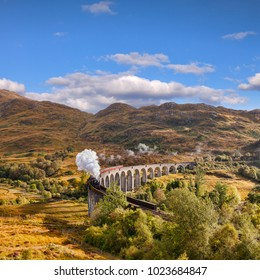 Glenfinnan Viaduct and the Jacobite steam train blowing steam from the exhaust as it crosses the Glenfinnan Viaduct, Highland, Scotland, UK.