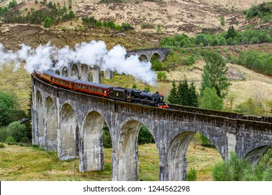 Glenfinnan Viaduct, Scotland. Travel/tourist destination in Europe. Old historical steam train riding on film scene famous viaduct bridge. Highlands, mountains, outdoor background.
