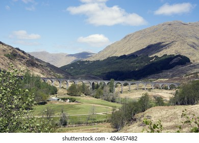 The Glenfinnan Viaduct. The Glenfinnan Viaduct is visable through the centre of this image. Behind we see the rugged mountains of the Scottish Highlands, in front the flat plane of the Highland glen.