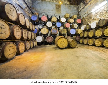 Glengoyne Distillery, SCOTLAND - SEPT 12, 2017 : Old wooden barrels and casks at Glengoyne whisky distillery established in 1833,  near Glasgow, with the mountains of Loch Lomond in the distance.