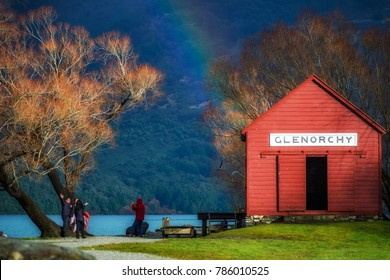 Glenorchy, New Zealand - July 14, 2014: Tourists photographing each other at the edge of Lake Wakatipu in Glenorchy, a remote village in New Zealand's  picturesque South Island.