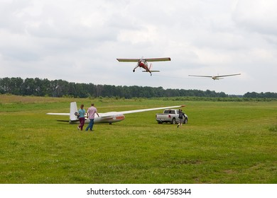Glider being towed into the sky by light aircraft. Automobile  towing  glider on the airfield for the takeoff point. People accompany glider. Man supports the wing trailed along the ground glider.