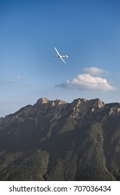 A glider performs a turn over the mountain