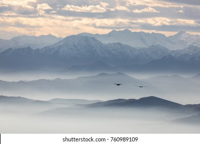 A glider pulled by a small plane flying over a mountainous landscape