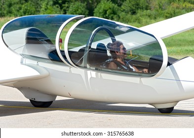 glider or sailplane passenger seated in cockpit waiting for takeoff from runway