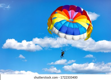 Gliding using a parachute on the background of cloudy blue sky.