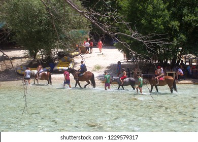 """Gliki, Thesprotia / Greece - 07/18/2018: Horse riding at the famous from greek mythology, acheron river. Acheron was known as the """"river of woe"""", and was one of the five rivers of the Greek underworld"""