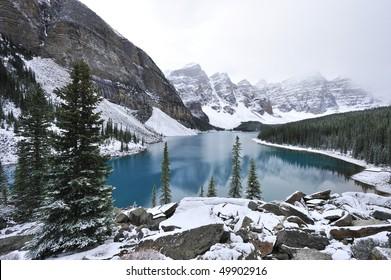 Glimmering crystal sapphire blue of Moraine Lake framed with ten snow peaks standing white-gray in morning fog Banff
