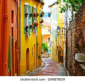 Glimpse of a narrow road in Menton, France. Bright, yellow colored houses surround the bricks encased on the wet floor. Flowers adorn the windows of the yellow house on the left.