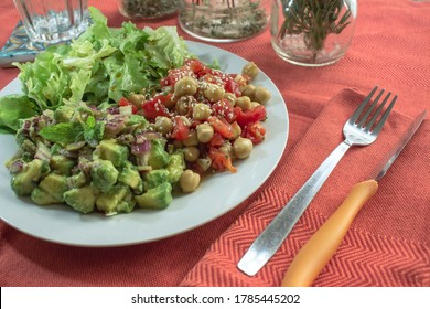 Glimpse on a table with red tablecloth with a vegan plate with a trio of salads: chickpeas and tomatoes, avocado and lettuce. In the background jars with aromatic herbs inside.