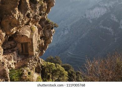 Glimpse of a stone cabin embedded in a rock wall along the Path of God ( Il sentiero degli dei)  mediterranean landscape, Campania, Southern Italy, Europe.