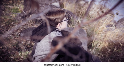 A glimpse through the bushes of a boy with glasses sitting by the lake on a chilly Autumn day. The foreground is a blur of a branch while focused on the boy's face.