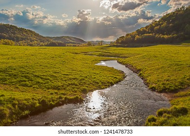 A glistening trout stream winds through an open verdant pasture between forested hills under a dramatic sky of clouds and bright sun beams