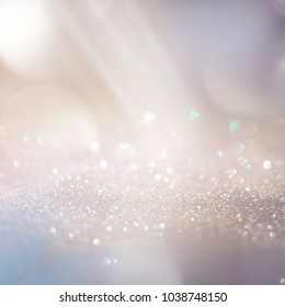Glitter background in pastel delicate beige and pearl tones, de-focused, free space.