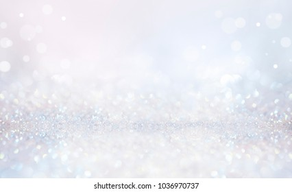 Glitter christmas background in pastel delicate silver and white tones de-focused.