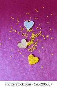 Glitter confetti three hearts and golden stars on purple background