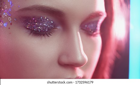 Glitter eyes. Creative fashion makeup. Woman face with sparkles on skin in pink neon light.