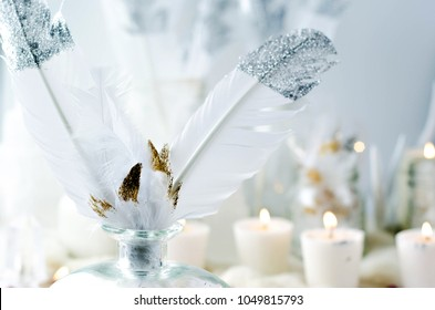 glitter feathers in jar with candles on white background